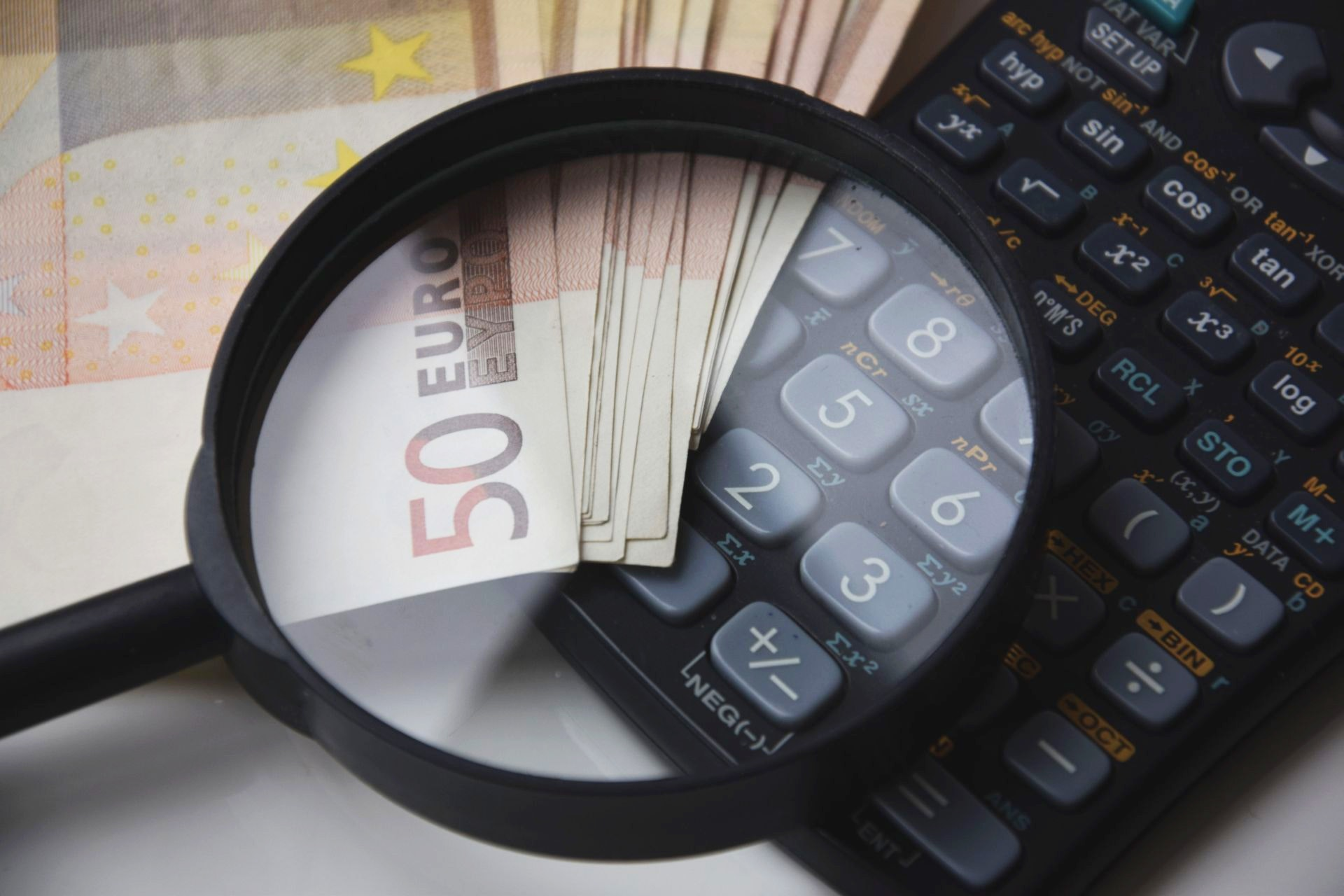 calculate-calculator-close-up-magnifying-glass-221174